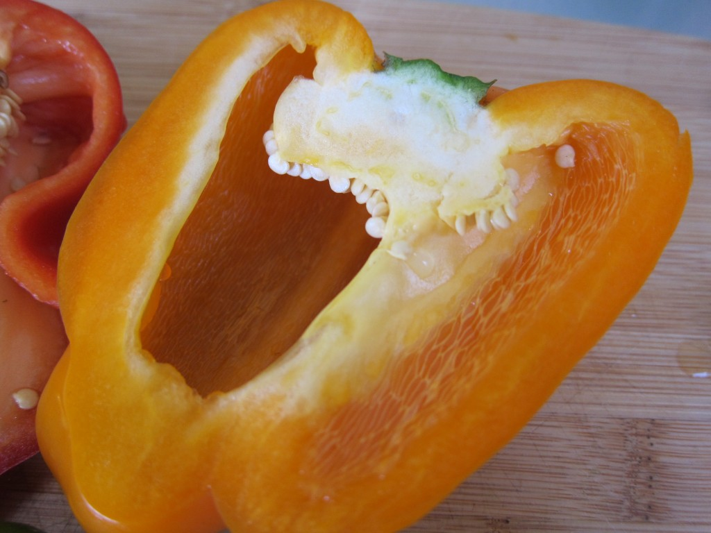 One half yellow pepper with stem, seeds and pith